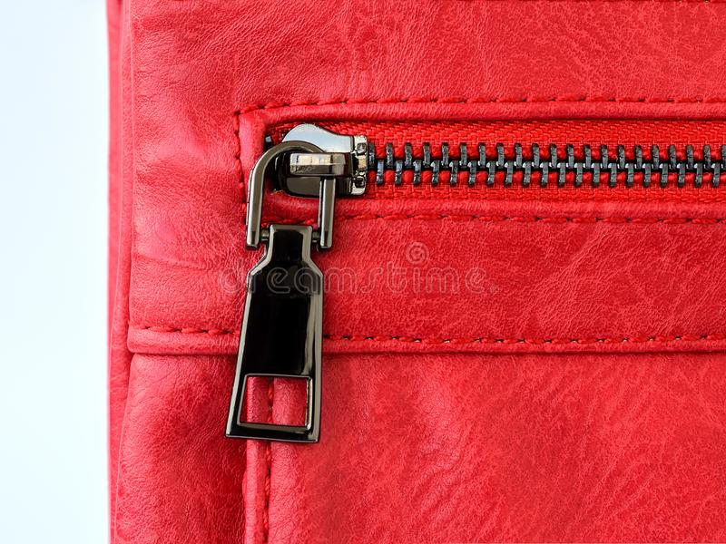 Zip pocket of a small red casual handbag. Fashionable modern accessories made of artificial or genuine leather. Close-up royalty free stock photography