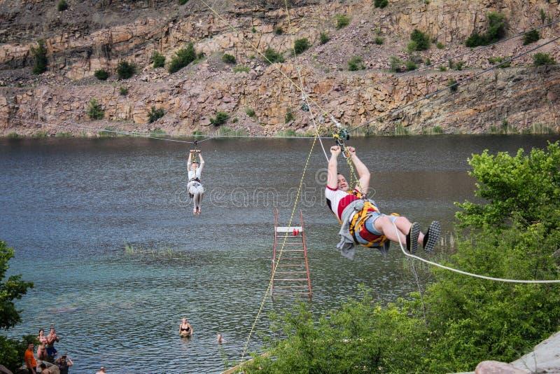 Zipline De man in het materiaal glijdt op een staalkabel Karretjespoor over het meer extreem royalty-vrije stock afbeelding