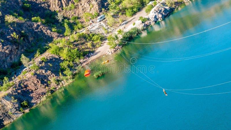 Zipline Istota ludzka w wyposażeniu ono ślizga się na stalowym kablu Tramwaju ślad Nad jeziorem Ekstremum i aktywnego odpoczynek obraz stock