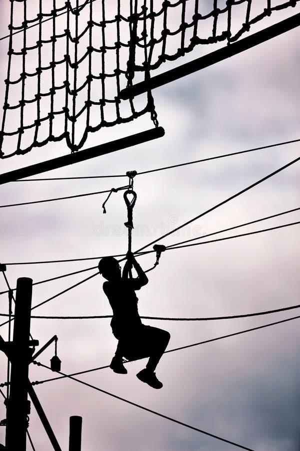 ziplining在邮编线的一个十几岁的男孩的剪影 库存图片