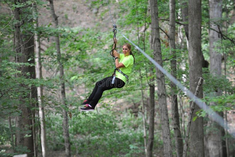 ziplining的妇女 免版税库存图片
