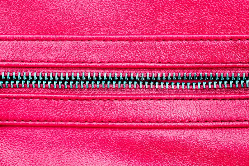 Zipper open between two layers of pink fabric textile and pink leather with visible seam under high magnification close detail. Photography as texture stock photo