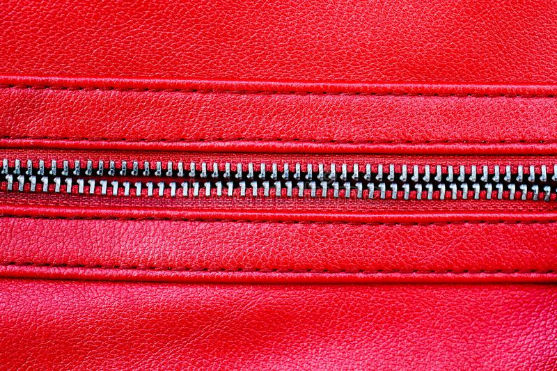 Zipper open between two layers of red fabric textile and red leather with visible seam under high magnification close detail. Photography as texture background royalty free stock photo