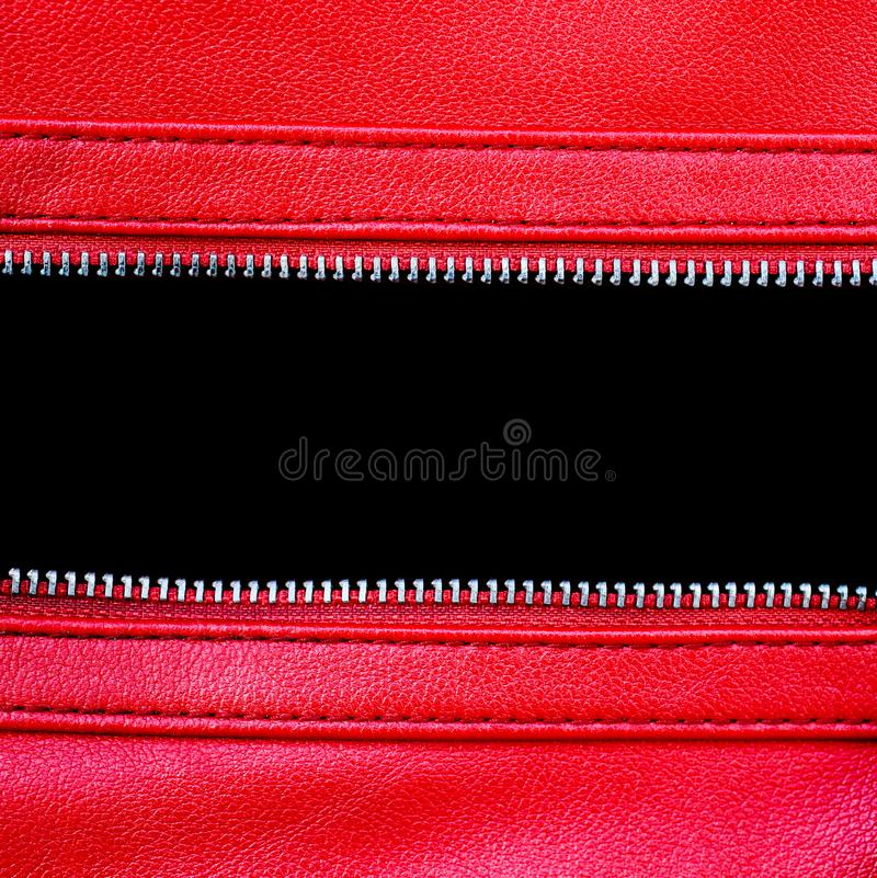 Zipper open between two layers of red leather fabric with visible seam under high magnification close detail. Photography as texture background with empty stock image