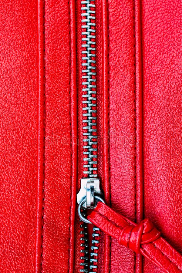 Zipper partly open close up detail macro photo on a red leather texture background in vertical format.  stock images