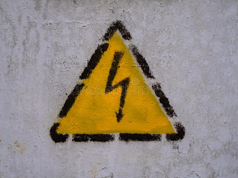 Zipper sign in the yellow triangle on the common wall. Dangerously high voltage royalty free stock image