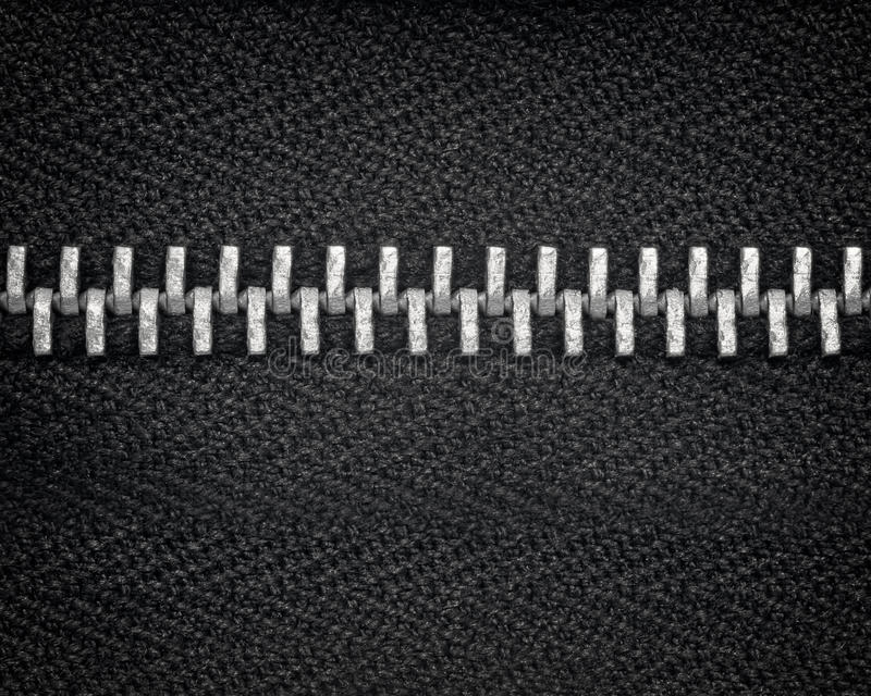 Zipper teeth close up with black fabric. A macro close up photograph of a closed sliver zipper and black cloth fabric stock images