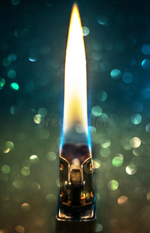 Zippo lighter closeup with flame bokeh background stock image