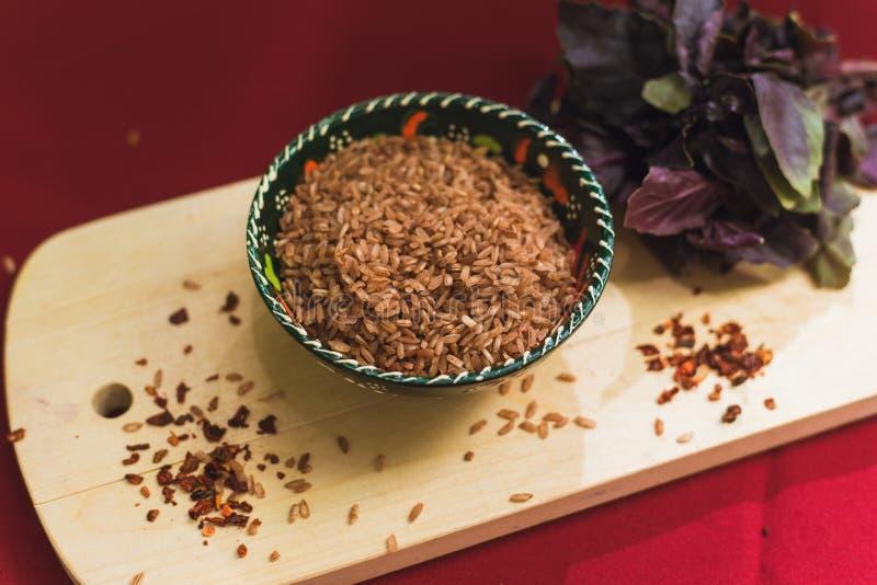 Zira ris ligger i en orientalisk platta mörkt ris ligger på en orientalisk bakgrund, en guld- bordduk, en träskärbräda bredvid arkivbilder