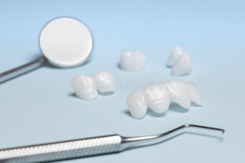 Dental tools and Zircon dentures on a blue background - Ceramic veneers - lumineers royalty free stock images