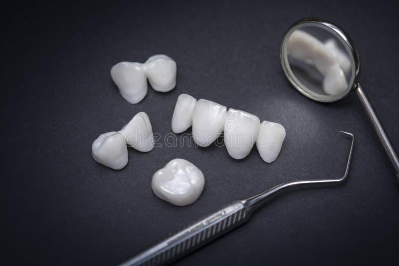Zircontandproteser och tand- hjälpmedel på en mörk bakgrund - keramiska fanér - lumineers arkivfoto