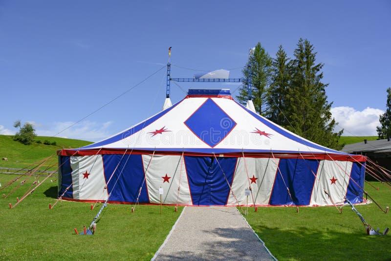 Zirkuszelt, kleines Zirkuszelt in Blauem und in weißem mit roten Sternen auf grüner Wiese lizenzfreies stockbild
