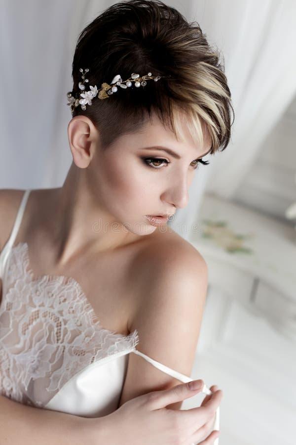 Zit de ochtend mooie gevoelige bruid met sexy kort haar met een zachte kleine kroon op zijn hoofd in een witte zijdelingerie in w stock foto's