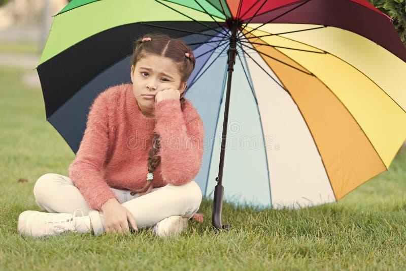 Zit het eenzame droevige gezicht van het meisjeskind park onder paraplu Positief en optimistisch verblijf Kleurrijke bijkomende p royalty-vrije stock afbeelding