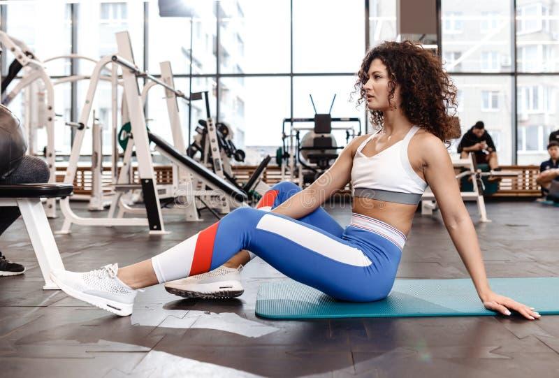 Zit het slanke krullende donker-haired meisje van Nice gekleed in sportenkleren op de mat voor fitness in de moderne gymnastiek m royalty-vrije stock afbeelding
