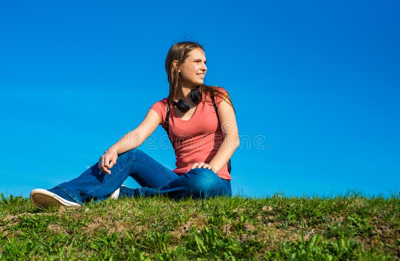 Zit het tiener donkerbruine meisje in koraalt-shirt met lang haar op het gras op hemelachtergrond met exemplaarruimte stock foto's