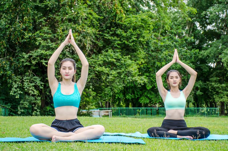 Zit mooie jonge vrouw twee meditatie doend yoga in park Het ontspannen en het mediteren terwijl wordt omringd van nature in de zo royalty-vrije stock foto