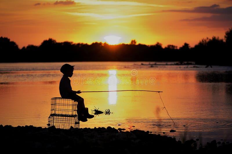 A zit op de rivier en vangt vissen Een foto van het silhouet onder de zon royalty-vrije stock afbeeldingen