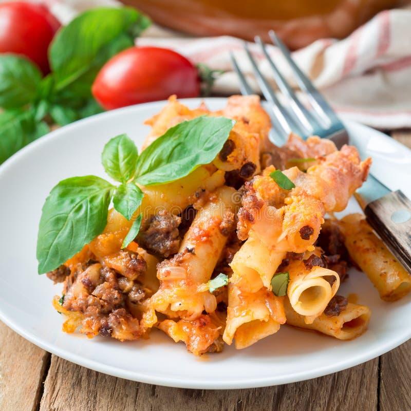 Ziti boloñés en una placa blanca, cazuela de las pastas con la carne picadita, salsa de tomate y queso, cuadrado imágenes de archivo libres de regalías