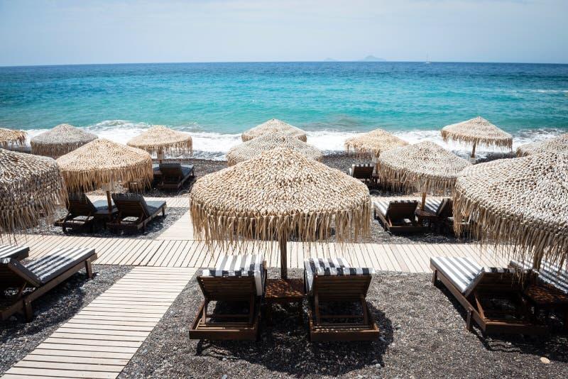 Zitkamerstoelen met paraplu's op het lege Witte strand, Santorini stock foto