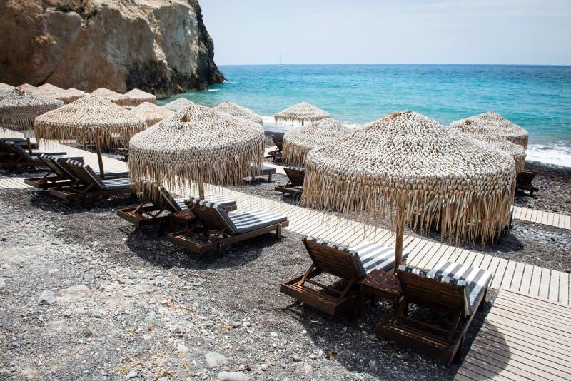 Zitkamerstoelen met paraplu's op het lege Witte strand in Santorini stock afbeelding