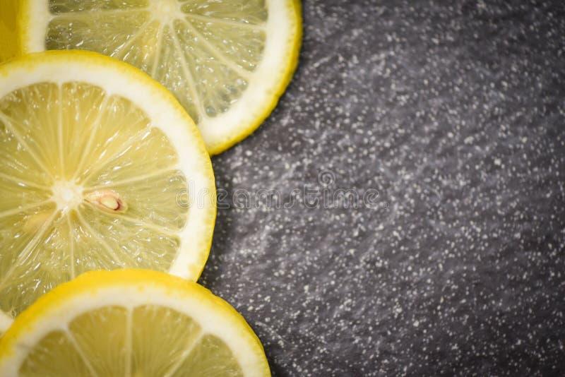 Zitrone auf dunklem neuem reifem Zitronenscheibenplatz auf SteinDraufsicht der hintergrundZitrusfrucht stockbilder