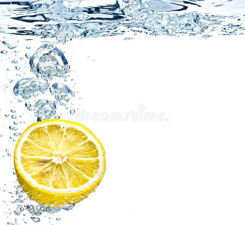 Zitrone, die im Wasser spritzt stockbild