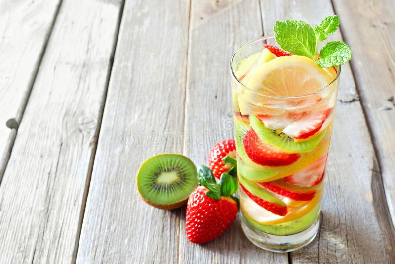 Zitrone, Erdbeere, Kiwi Detoxwasser gegen rustikales Holz lizenzfreies stockbild