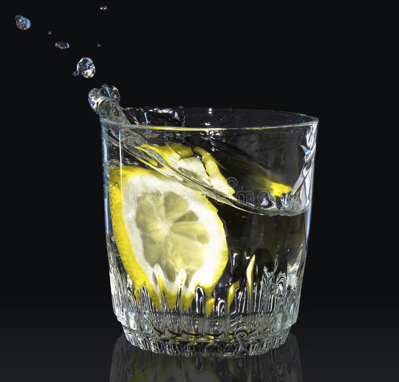 Zitrone fiel in ein Glas Wasser lizenzfreies stockfoto