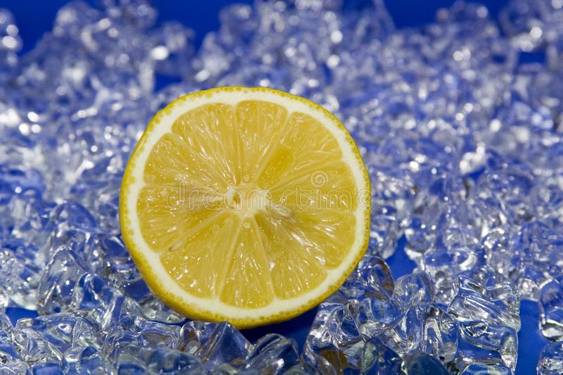 Citron halfed. Fresh yellow citron on cold ice with blue stock photo