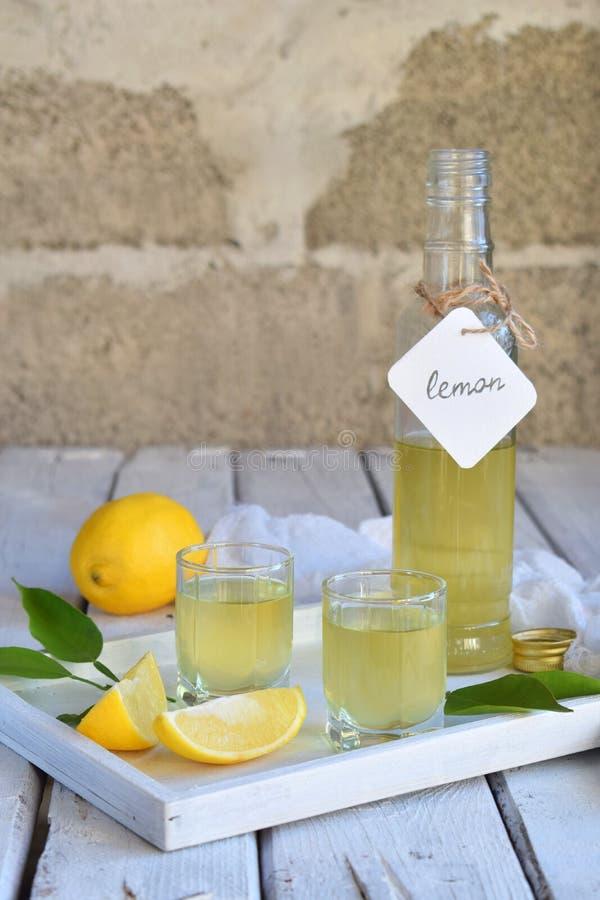 Zitrone-gewürzter italienischer Likör im Glas Köstliches gelbes Alkoholgetränk Limoncello-Alkohol Glasflasche, Schuss und Zitrusf stockfotografie