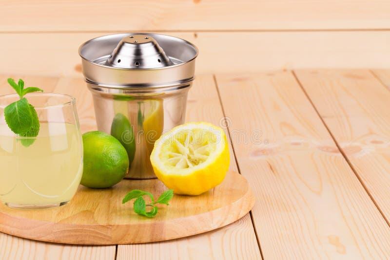 Zitrone Juicer mit Saft auf hölzernem Hintergrund stockfotografie