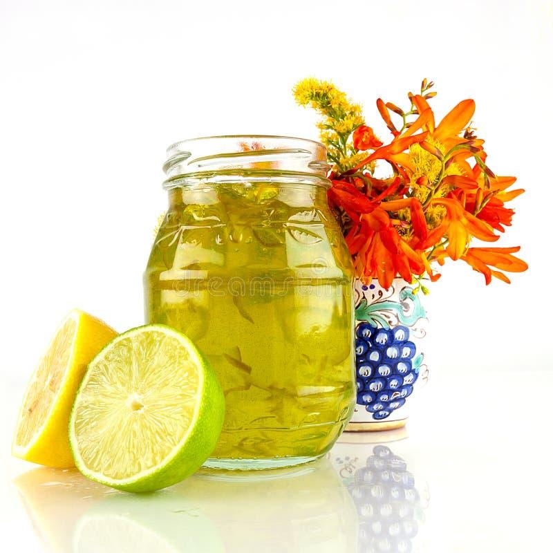 Zitrone, Kalkmarmelade und Gartenblumen stockbild