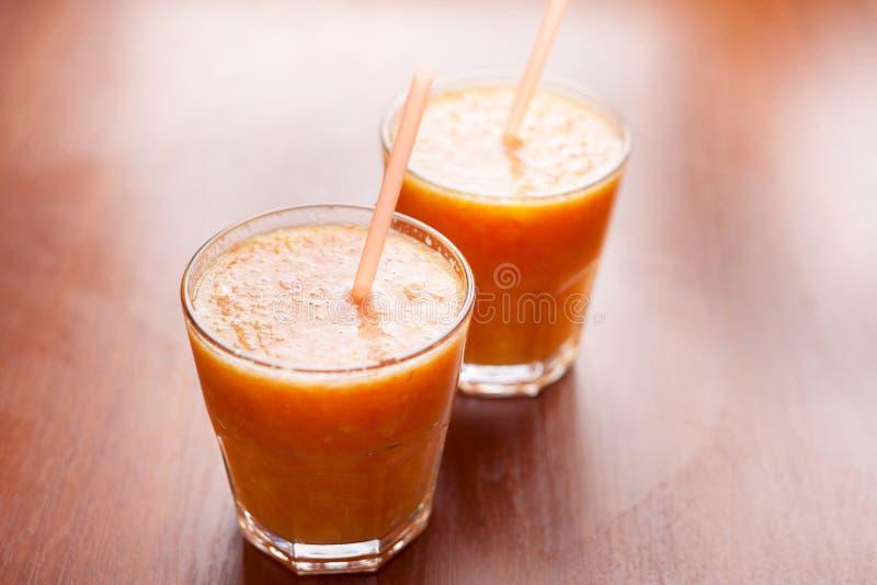 Zitrone und orange Smoothies auf dem Tisch mit Scheiben der Zitrone und der Orange in den Schalen eines Glases mit Rohren lizenzfreie stockfotografie
