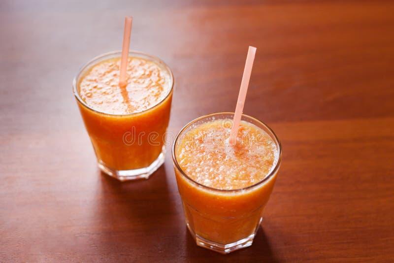 Zitrone und orange Smoothies auf dem Tisch mit Scheiben der Zitrone und der Orange in den Schalen eines Glases mit Rohren lizenzfreie stockbilder