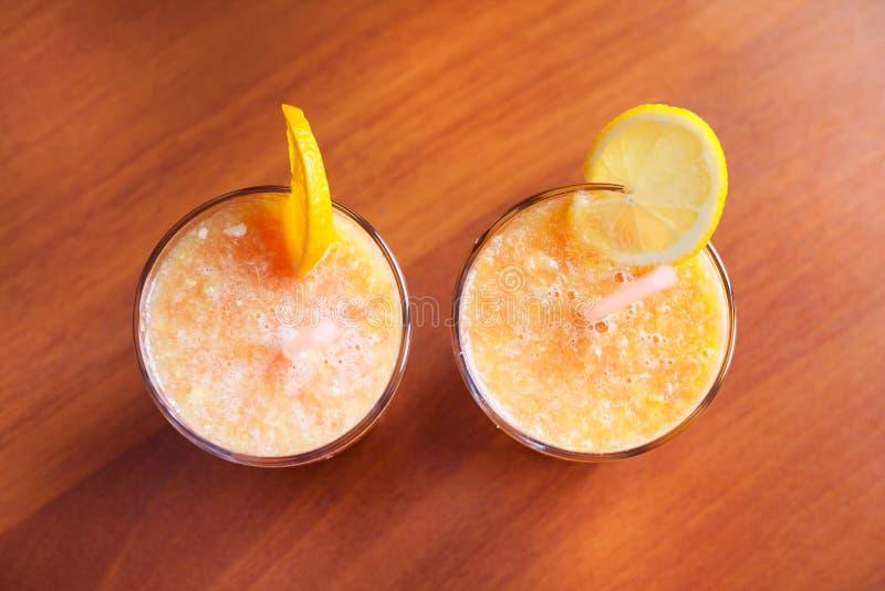 Zitrone und orange Smoothies auf dem Tisch mit Scheiben der Zitrone und der Orange in den Schalen eines Glases mit Rohren stockfotos