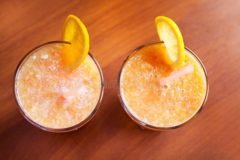 Zitrone und orange Smoothies auf dem Tisch mit Scheiben der Zitrone und der Orange in den Schalen eines Glases mit Rohren lizenzfreie stockfotos