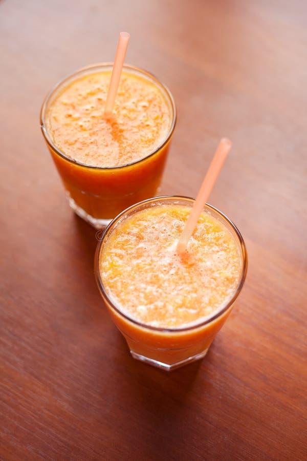 Zitrone und orange Smoothies auf dem Tisch mit Scheiben der Zitrone und der Orange in den Schalen eines Glases mit Rohren stockbild