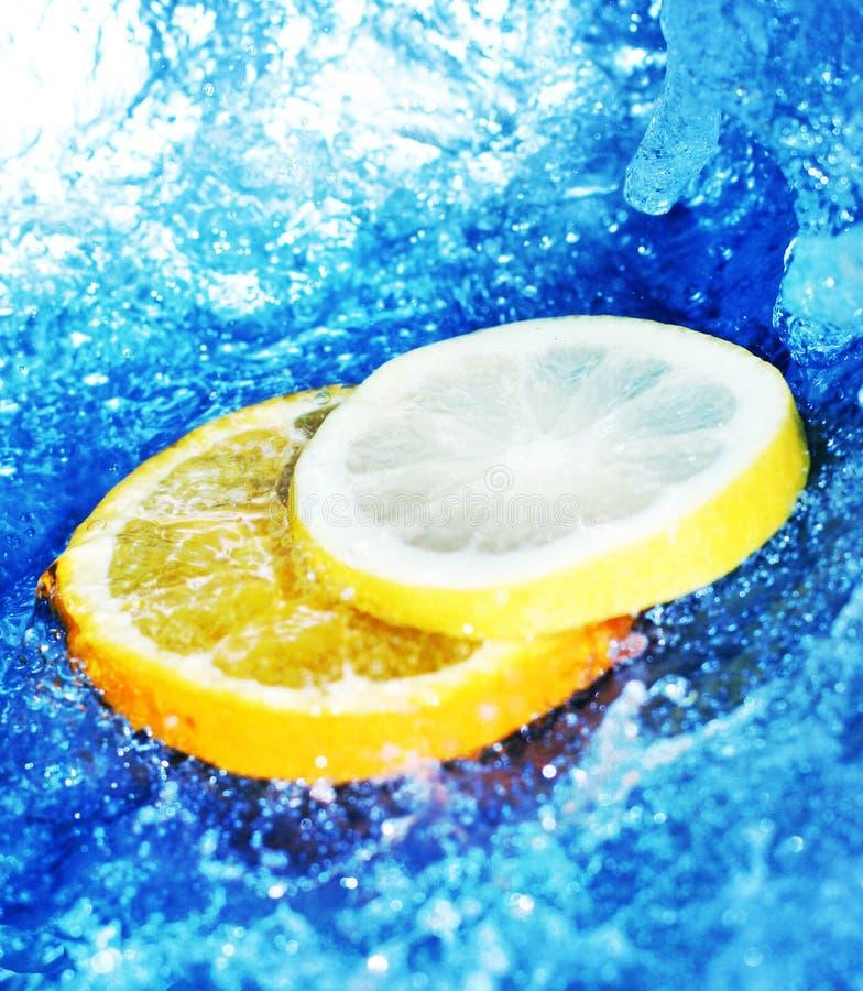 Zitrone und Orangen mit Wasser stockfotografie