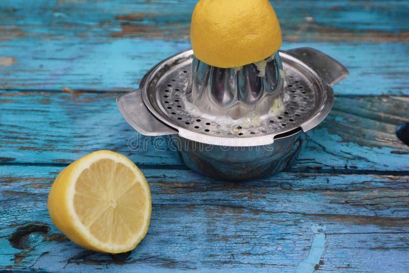 Zitronen-Hälften, die Juiced im Metalljuicer sind lizenzfreie stockfotos