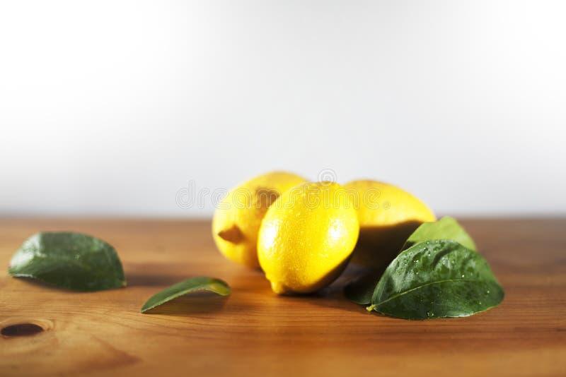 Zitronen mit Blättern auf einem Holztischbrett lizenzfreies stockfoto