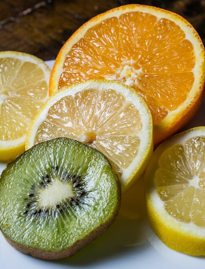 Zitronen-Orange und Kiwi auf weißer Platte stockfotos