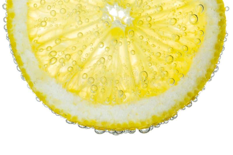 Zitronen-Scheibe im klaren sprudelnden Wasser-Blasen-Hintergrund lizenzfreie stockfotografie