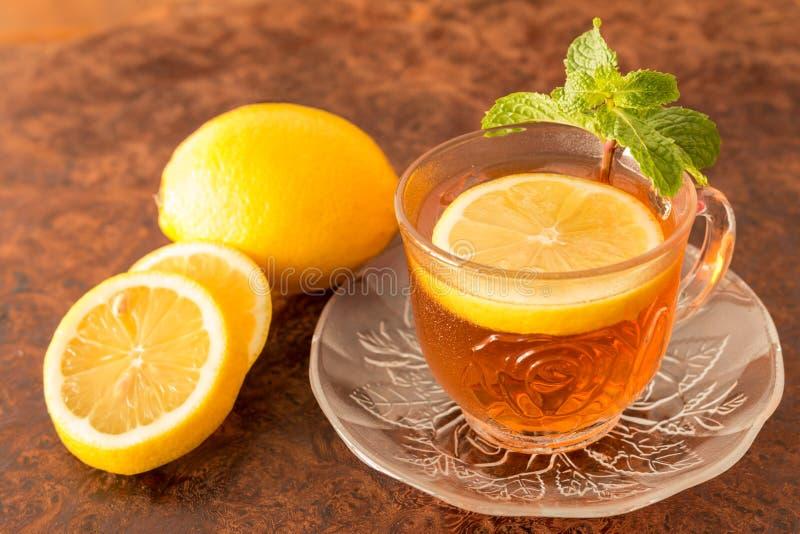 Zitronen-Tee - Schale Zitronenscheiben mit Tee und Minze treiben Blätter stockfoto