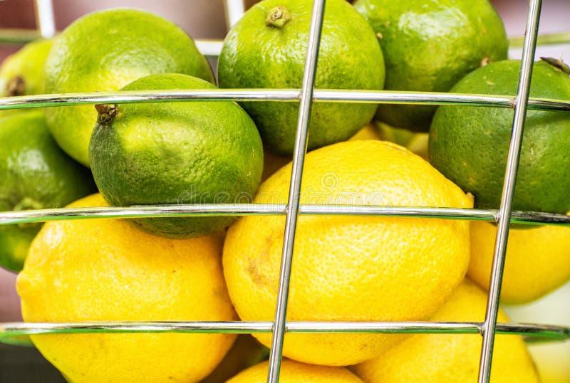 Zitronen und grüne Kalke im Metallkorb, Abschluss herauf Fruchtszene stockfotos
