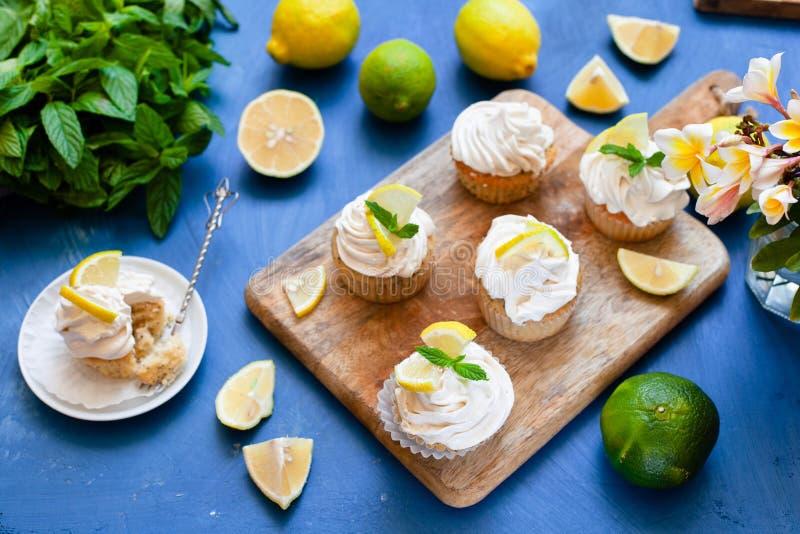 Zitronenkuchen mit Mohnsamen, weißer Buttercreme und Zitronenschnitzel stockbild