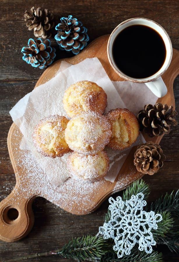 Zitronenmuffins, Tasse Kaffee, Kiefernkegel häkelten Schneeflocke lizenzfreie stockfotografie