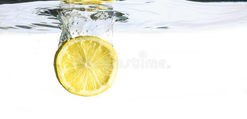 Zitronenscheibe fällt in das Wasser, lokalisiert auf einem weißen backg stockbild