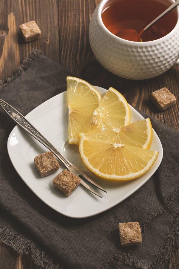 Zitronenscheiben, brauner Zucker und eine Tasse Tee auf einer hölzernen rustikalen Tabelle Selektiver Fokus getont stockbild