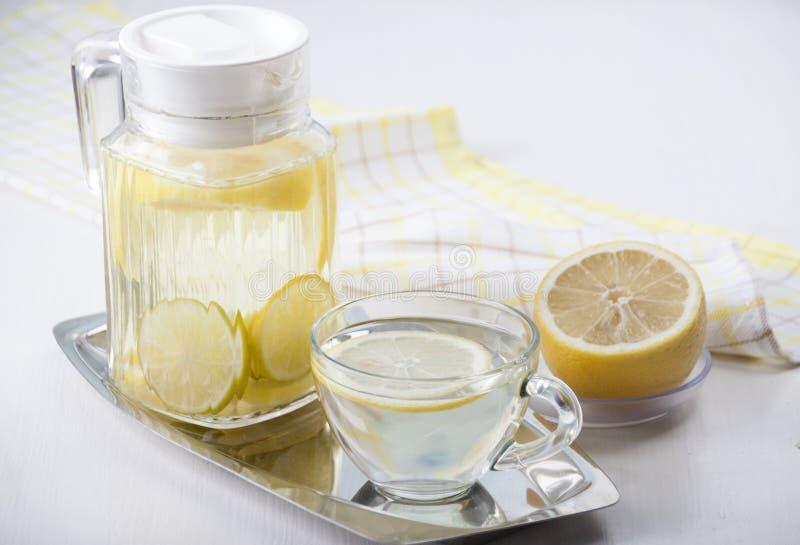 Zitronenwasser in einem Glaskrug und in einer Glasschale stockbild